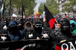 Masked demonstrators gather ahead of labour unions at the traditional May Day labour march in Paris, France. REUTERS/Gonzalo Fuentes