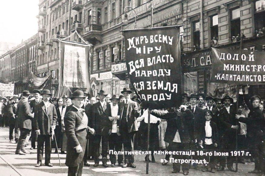 """Manifestação política em 18 de junho de 1917, em Petrogrado. No banner à esquerda lê-se: """"Paz para todos - Todo o Poder ao Povo - Toda Terra para o Povo"""" e no banner à direita lê-se: """"Fora os ministros-capitalistas""""; estas eram palavras de ordem Bolcheviques."""