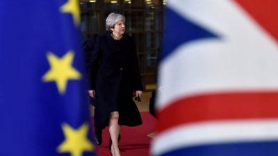 Theresa May, na reunião do Conselho Europeu, entre as bandeiras da União Europeia e a de seu país