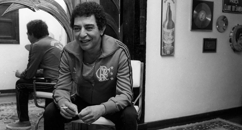 João Nogueira, em casa. Usa um casaco com o escudo do Flamengo. Foto Blog Arquivos do Samba Na parede, discos de ouro e uma placa de rua, escrito Praça Clube do Samba