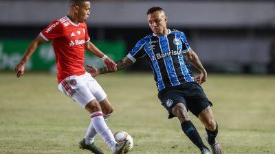 Um jogador do Internacional conduz a bola enquanto jogador do Grêmio se aproxima