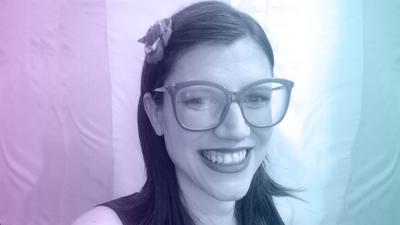 travesti socialista. Ela usa óculos, esta´com uma flor presa ao cabelo e usa batom. Está sorrindo.