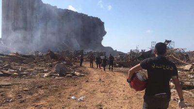 Um bombeiro, caminha em direção ao prédio ao local da explosão, de onde sai fumaça