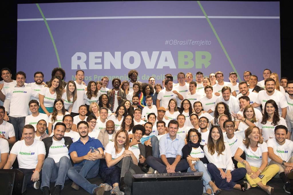 Cerca de 50 pessoas posam para foto. Ao fundo, um painel, com a logo do RenovaBR