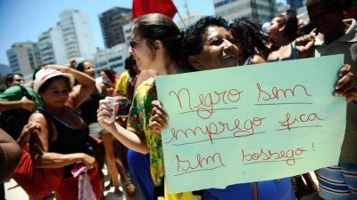 """Mulher negra segura um cartaz feito à mão em uma manifestação: """"Negro sem emprego fica sem sossego"""". Ela sorri. Há outras pessoas na foto, uma bandeira ao fundo."""