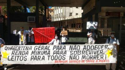 """Trabalhadoras da saúde protestam em frente a um hospital no Rio de Janeiro. Na faixa que seguram, está escrito: """"Quarentena geral para não adoecer. renda mínima para sobreviver, leitos para todos não morrer. Nenhum serviço de saúde a menos."""