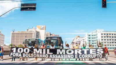 Uma faixa preta com letras brancas é aberta em uma rua, diante do trânsito. Escrito 100 mil mortes. Bolsonaro assassino.