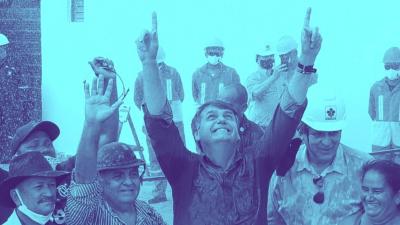 Bolsonaro sorri e está com as duas mãos para cima, apontando, e olhando para cima. Ao seu lado, moradores. um deles com chapeu sertanejo. Uma mulher sorri. Ninguém usa máscara. Ao fundo, uma fileira de operários observa.