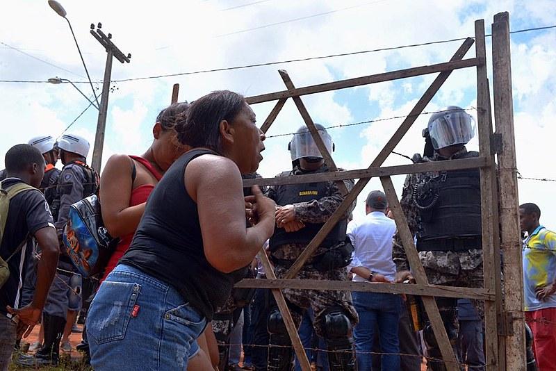 Moradora, negra, entre 40 e 50 anos,gesticula e apela aos policiais militares no Cajueiro. Entre eles há uma portão.