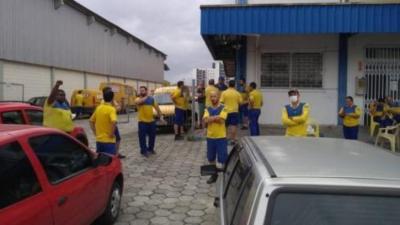 Na foto, estão cerca de 10 trabalhadores dos correios, no pátio de uma unidade da empresa