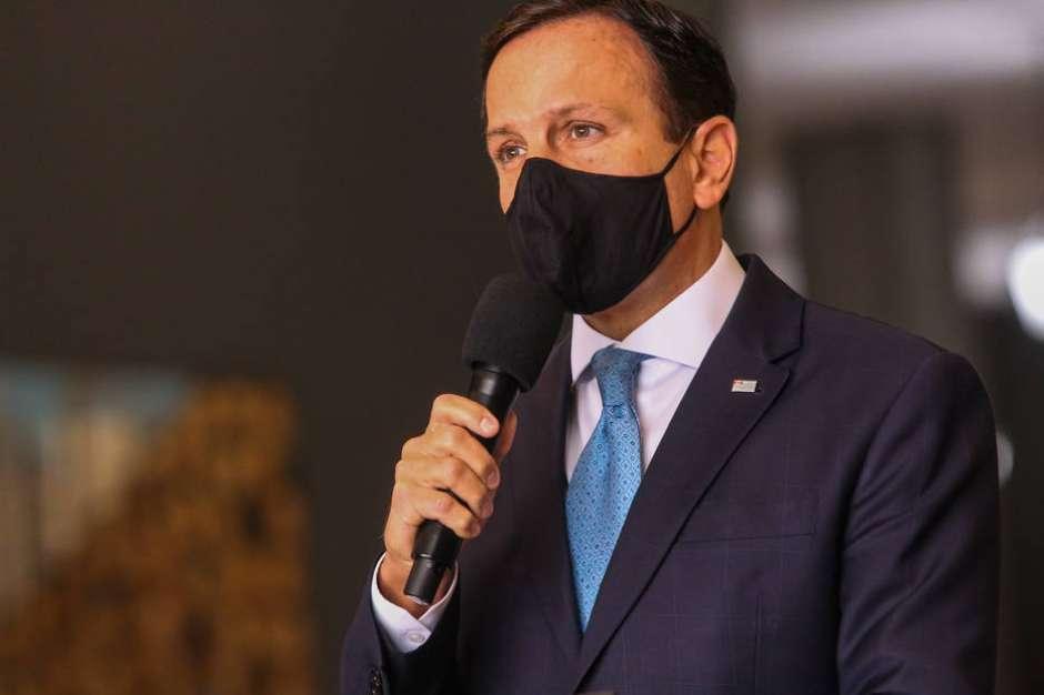 João Doria, falando ao microfone, de máscara