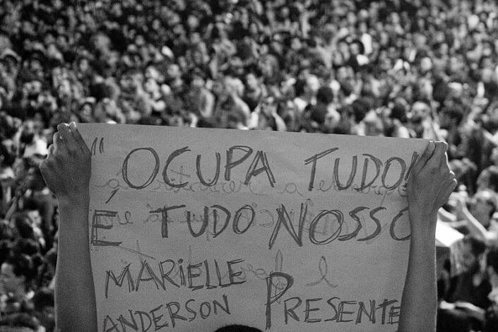Uma mulher levanta um cartaz com os dizeres: Ocupa Tudo, é tudo nosso, Marielle e Anderson presentes!. Ao fundo, uma multidão.