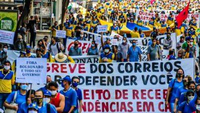 Imagem de manifestação da greve, com centenas de pessoas. uma faixa está na frente do ato, com os dizeres. Greve dos Correios: é para defender você