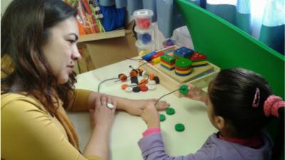 Professora acompanha aluna que utiliza brinquedos educativos, para estímulo da coordenação motora