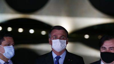 Os três estão com máscara em solenidade ao ar livre, à noite. Ao fundo, o Palácio do Alvorada
