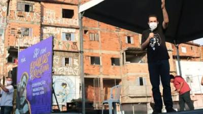 Boulos discursa em um palco. Ele está com máscara e camisa preta. Ao lado, uma placa roxa com o nome dele e de erundina. Ao fundo, casas com tijolos aparentes