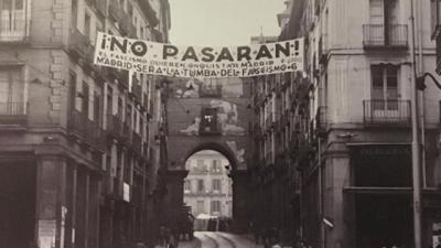 Fotografia histórica. Em Madrid, uma faixa estendida entre dois prédios, com a frase !No Pasaran! (Não passarão)