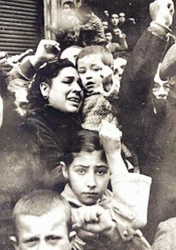 Uma mulher chora, com uma criança no colo. No centro da foto, logo abaixo da mulher, uma menina de cerca de 11 anos, olha fixamente para quem fotografa
