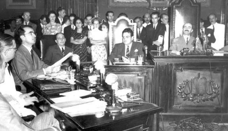 Um salão de reuniões. Uma cadeira ao centro, com quem preside a sessão. à esquerda, um homem discursa. Ao fundo, várias pessoas assistem à sessão.