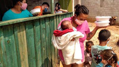 Uma mulher com uma criança no colo acaba de receber uma quentinha e está se asfatando do local. Atrás do balcão, em uma construção de madeira, uma mulher com máscara segura outra quentinha, para a próxima pessoa da fila. Há mais duas pessoas do lado de dentro. E duas crianças do lado de fora.
