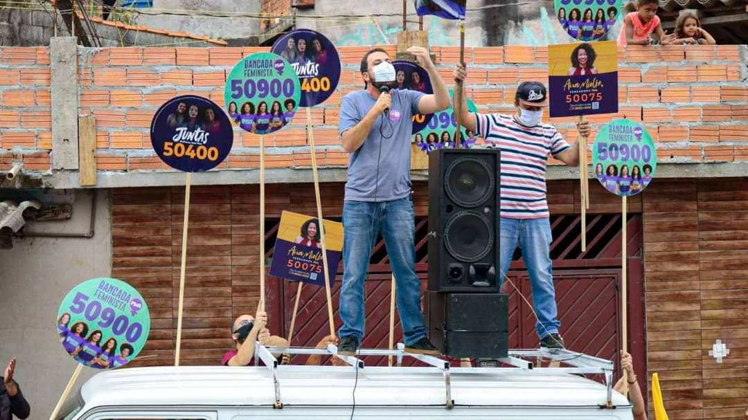 Guilherme Boulos discursa em cima de uma kombi, em atividade de campanha. Ele usa máscaras. Em torno dele, cinco ou seis pirulitos de campanhas para vereador(a).