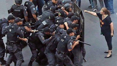 Uma professora aponta o dedo para uma coluna de policiais, que estão atrás de escudos. Imagem ficou famosa, por representar a bronca de uma educadora diante da violência policial contra os professores