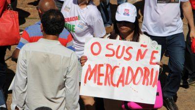 Imagem de um protesto. Uma servidora da saúde, com um boné, segura um carta: O SUS Ñ É MERCADORIA