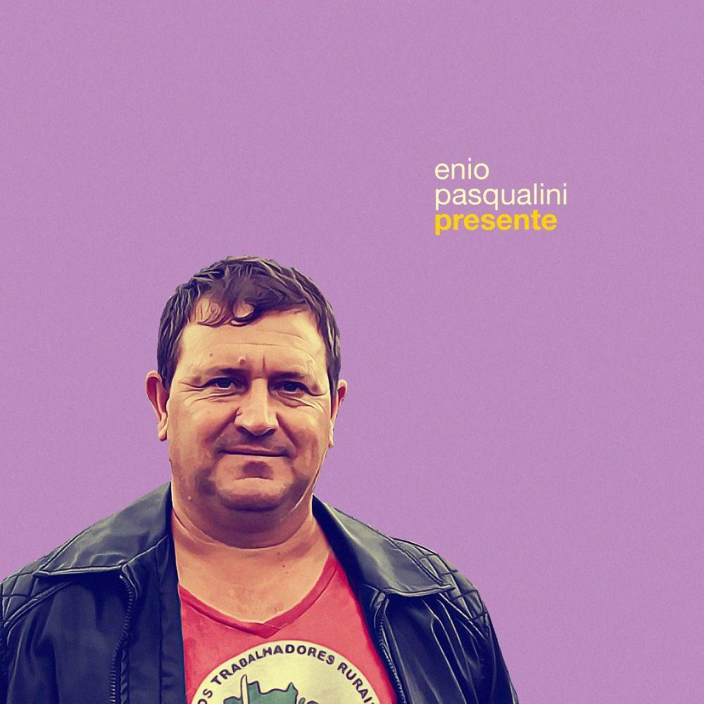 Foto de Enio Pasqualini, com camisa do MST e casaco preto. Acima, está escrito Enio Pasqualini presente.