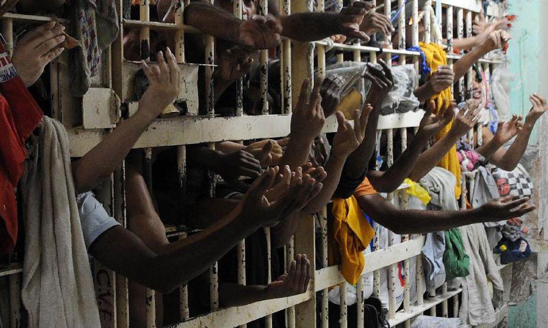 Foto de uma grade de uma cela, com superlotação. Vários detentos colocam as mãos para fora.