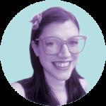 travesti socialista. ela está sorrindo, usa óculos e uma flor no cabelo.