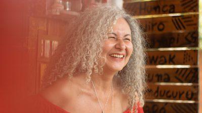 Lorene está sorrindo, de lado para a foto. Ela está com os cabelos soltos, compridos.