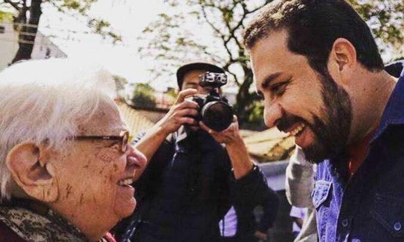 Erundina e Boulos estão de perfil e se olham, sorrindo. No fundo, entre eles, um fotógrafo registra a cena.