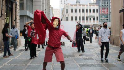 Ao centro da foto, um homem com bermuda e camisa vermelhas e a máscara de A Casa de Papel. Atrás dele, dois outros ativistas, seguram uma faixa. Algumas pessoas passam na rua de pedestres, no centro de SP