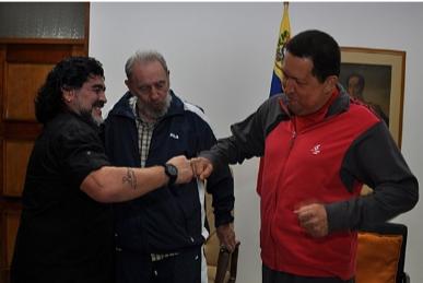 Maradona e Hugo Chávez se cumprimentam, sob o olhar de Fidel. Os dois sorriem e encostam os punhos. Ao fundo, na sala, um quadro com o retrato de Simon Bolivar