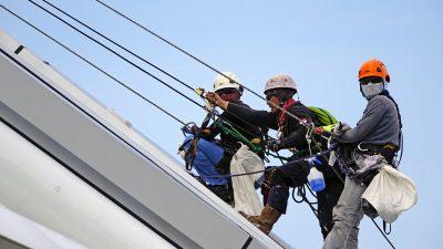 três trabalhadores estão escalando uma construção, segurando em cabos de aço. Eles usam capacetes e botas. Um deles olha em direção à câmera.