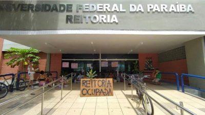 Foto da entrada da reitoria da UFPB. Com barracas e um cartaz onde se lê: Reitoria ocupada