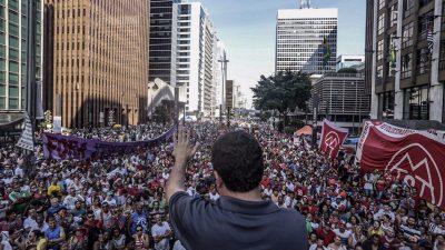 Guilherme Boulos, de costas para a foto, discursa para umma multidão na Avenida Paulista