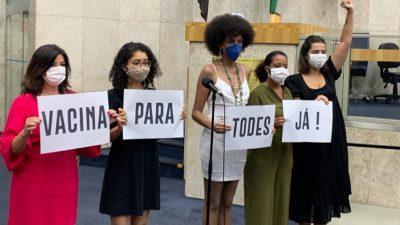 Covereadores seguram cartazes, formando a frase: Vacina para todes já!