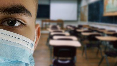 Detalhe do rosto de um aluno de máscara, ao fundo, uma sala de aula vazia