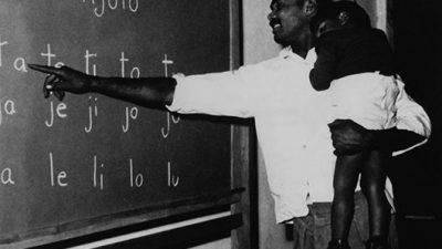 Um homem segura no colo uma criança e aponta para sílabas em um quadro escolar