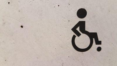 Fotografia. símbolo gráfico, representando uma pessoa em uma cadeira de rodas, sobre uma parede branca