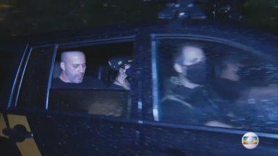 Deputado sendo levado preso no banco traseiro de um carro da policia.