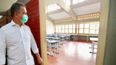Rui Costa, de máscaras, olha uma sala vazia em uma escola