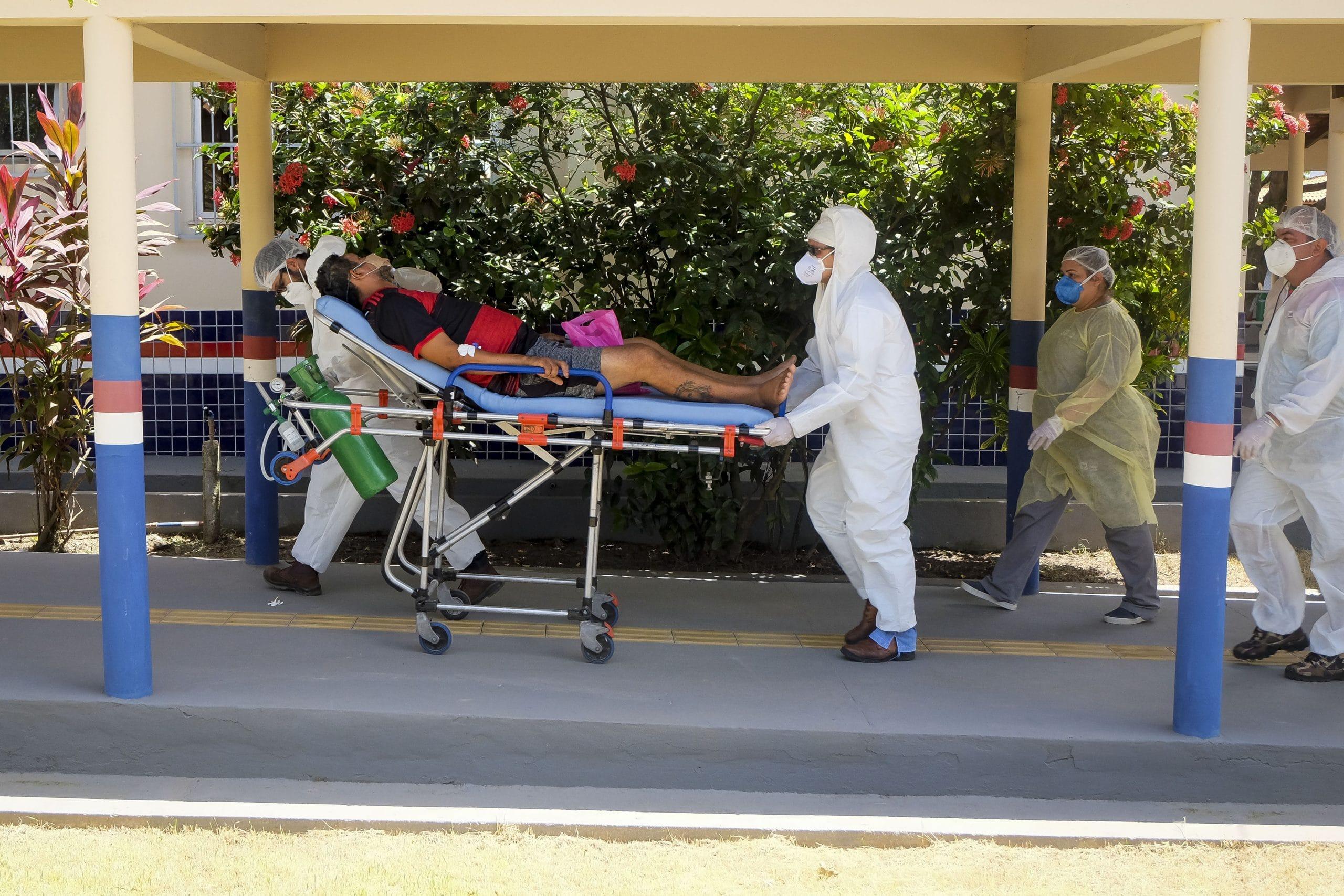 Dois profissionais da saúde carregam um paciente em uma maca. Eles usam mascaras e roupas de proteção brancas. O paciente é um homem, usa bermuda e camisa do flamengo.