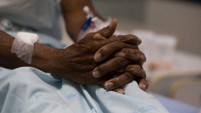Foto mostra mãos cruzadas de uma mulher idosa negra em um hospital