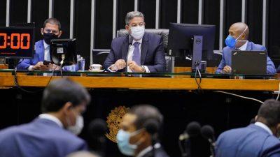 Presidente da Câmara, Lyra, preside sessão que votou a PEC 186. Ele usa máscara. A seu lado, dois deputados estão também sentados na mesa. No plenário, outros deputados conversam.