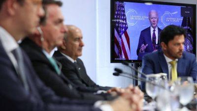 Bolsonaro e ministros estão sentados, com fones de ouvido. Ao fundo, a bandeira dos EUA e Joe Biden, discursando na Cúpula do Clima