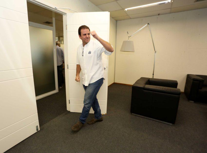 Eduardo Paes veste camisa, de fundo vemos o gabinete da prefeitura.