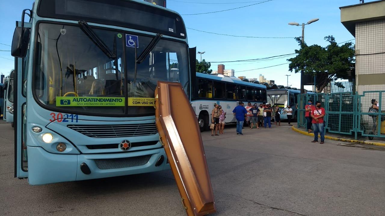 Fila de ônibus parados. Na frente do primeiro, um caixão bloqueia a passagem