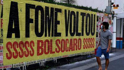 """Cartaz colado na rua, com a frase: """"A FOME VOLTOU!"""" abaixo: $$$$$ BOLSOCARO $$$$$. Um homem passa e observa o mural."""
